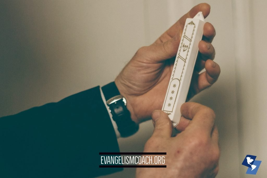 Hands holding a a Mezuzah before mounting it on a door post.  My neighbors posted one to their door.