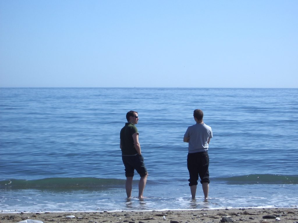 Two men standing in gentle surf