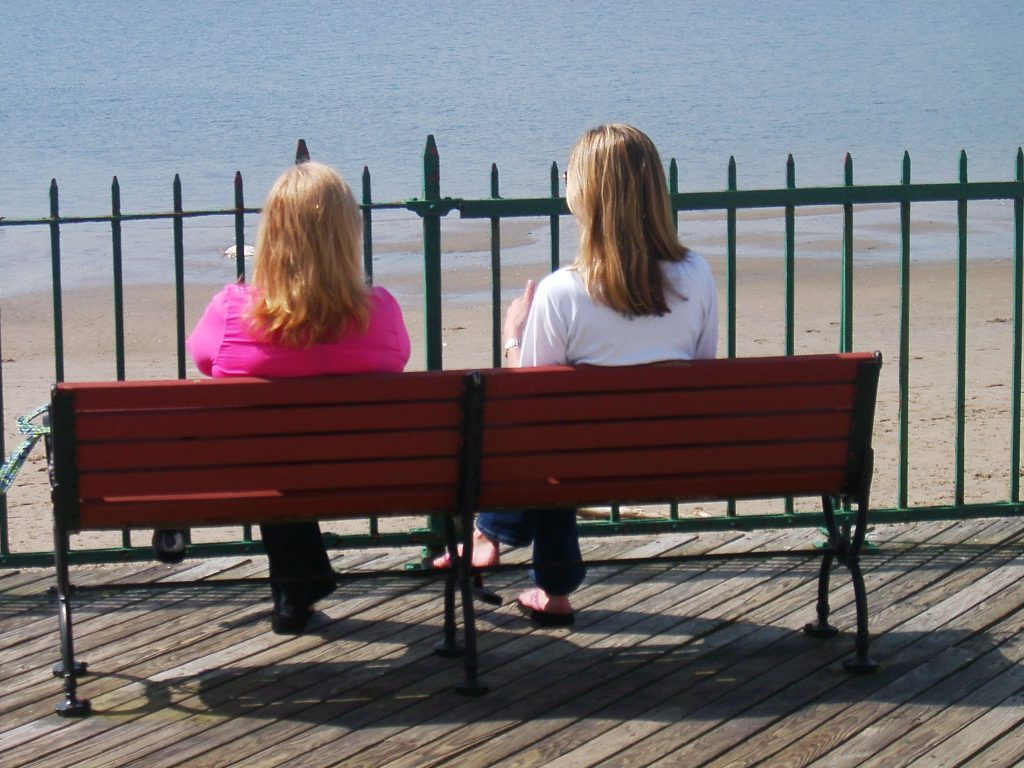 ...with your feet fitted with the readiness that comes from the gospel of peace.   Two women sit on an oceanfront bench perhaps to discuss the gospel
